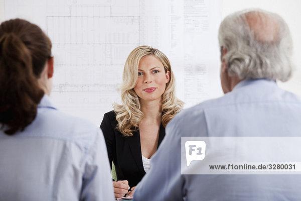 Geschäftsfrau im Gespräch mit Mann und Frau