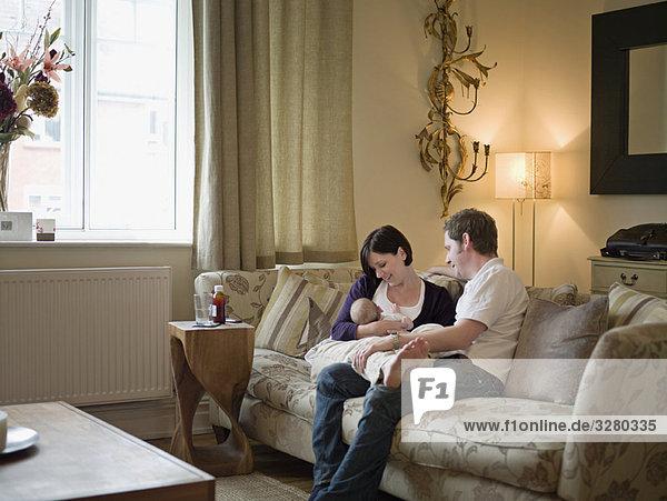 Ein Paar und ein neues Baby sitzend auf einem Sofa