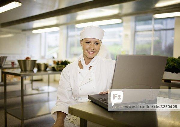 Eine Köchin  die an ihrem Laptop arbeitet.