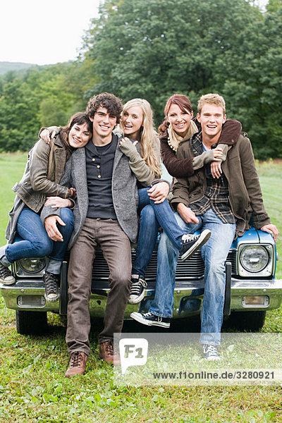 Freunde auf einem Auto sitzend