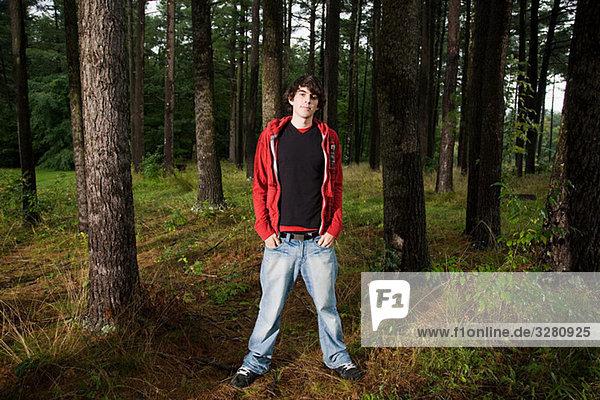 Junger Mann im Wald stehend