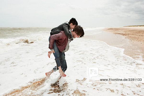Mann gibt Freundin Huckepack im Meer