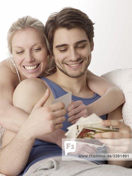 Fröhliches Paar auf der Couch schaut Fotos an