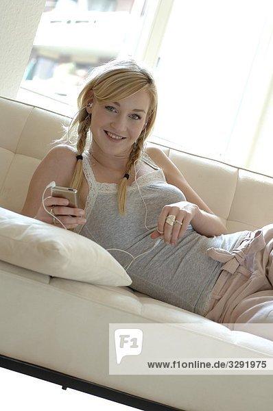 Teenagerin hört Musik auf der Couch