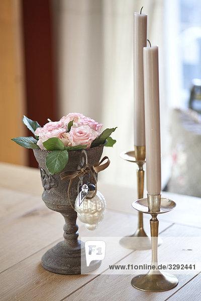 Blumen in einem Trinkgefäß neben zwei Kerzenständern
