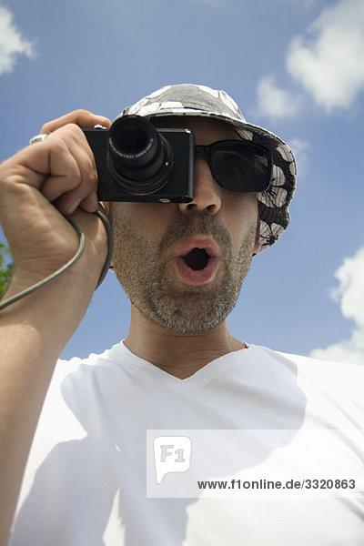 Ein Mann  der ein Foto mit einer Digitalkamera macht.