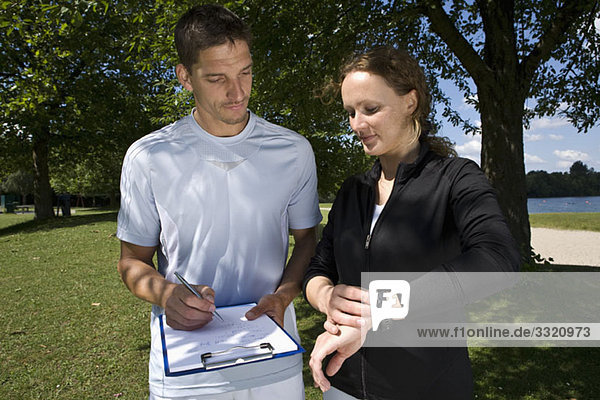Eine Frau mit einem Personal Trainer  der sich Notizen macht.