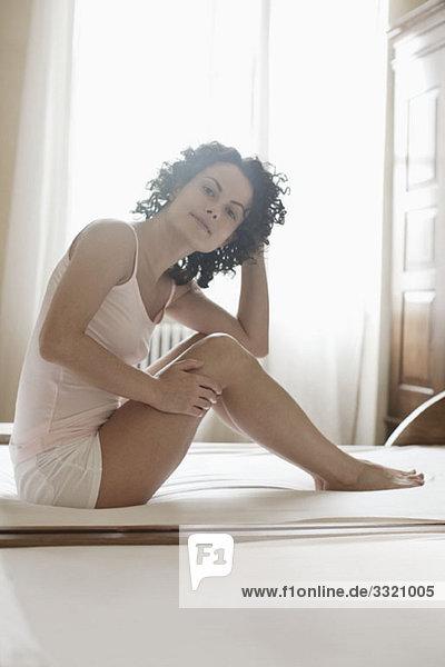 Eine Frau  die auf ihrem Bett sitzt.