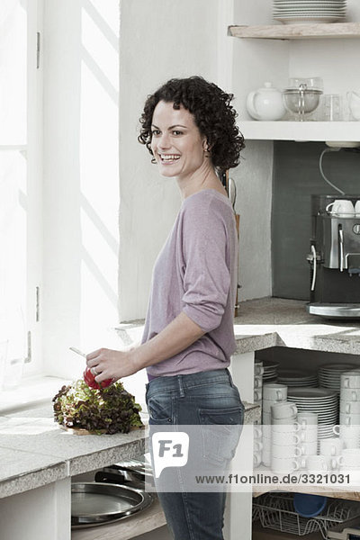 A woman preparing vegetables in the kitchen