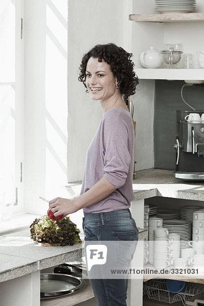 Eine Frau  die Gemüse in der Küche zubereitet.