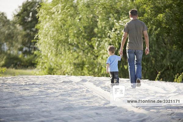 Rückansicht eines Mannes und eines Jungen  die Hand in Hand gehen.