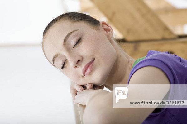 Eine Balletttänzerin  die ihren Kopf an der Stange in einem Ballettstudio auf die Arme legt.
