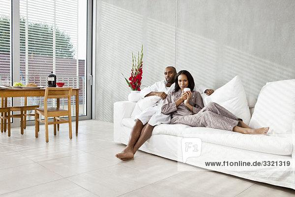 Ein junges Paar entspannt auf dem Sofa  morgens