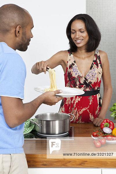 Eine junge Frau  die ihrem Freund Spaghetti serviert.