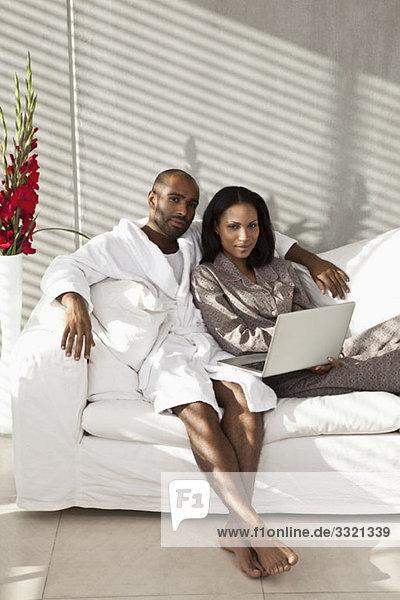 Ein Paar im Pyjama auf einem Sofa mit Laptop
