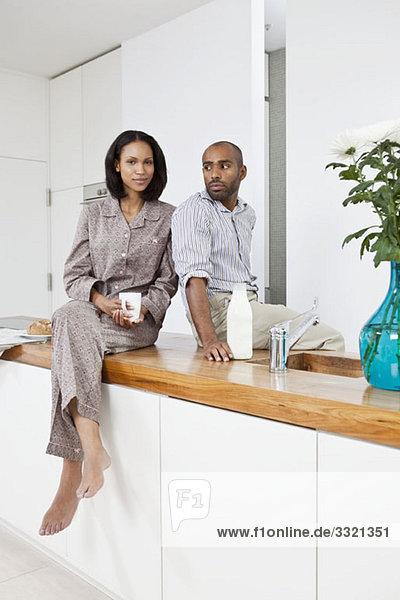 Ein junges Paar  das auf einem Küchentisch sitzt.