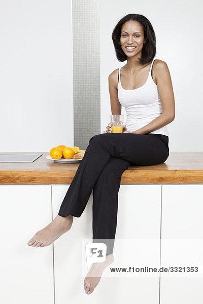 Eine junge Frau sitzt auf einer Küchentheke und hält ein Glas Orangensaft.