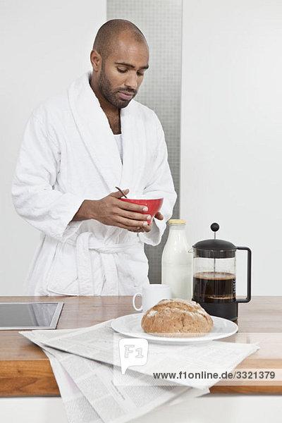 Ein Mann im Bademantel beim Frühstück.