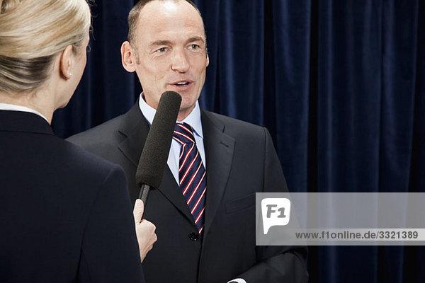 Ein Mann in einem Anzug  der verhört wird.