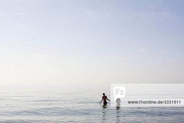 Zwei Menschen  die im Meer stehen.
