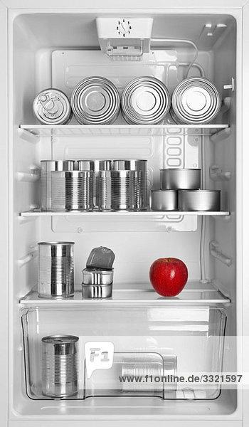 Diverse Blechdosen und ein Apfel im Kühlschrank