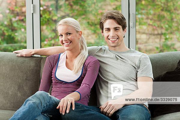 Junges Paar auf dem Sofa zu Hause sitzend