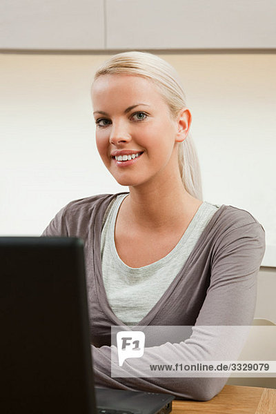 Young woman sitting at table with laptop