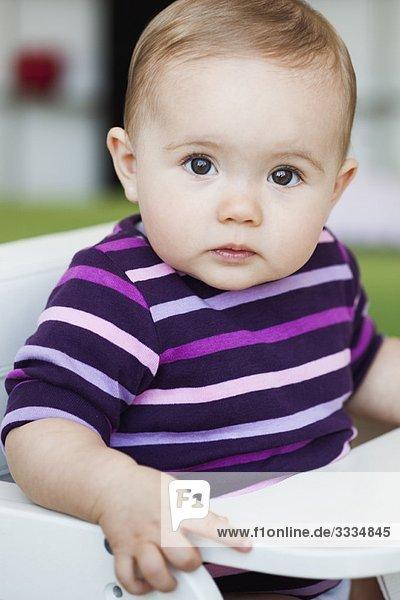 Baby sitzend im Stuhl mit Blick auf den Betrachter