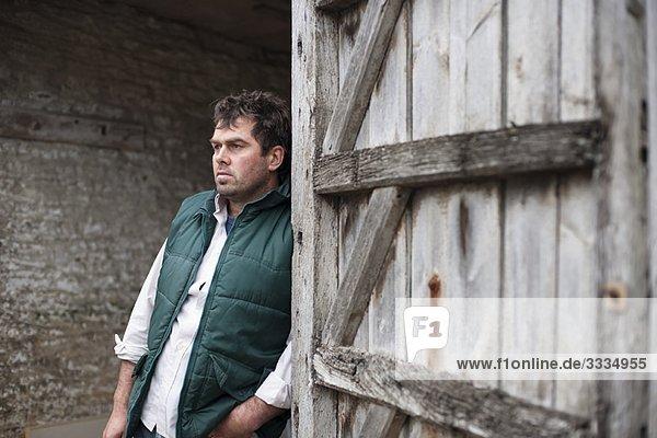 Bauer im Stall stehend