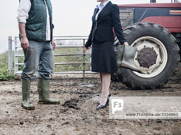 Geschäftsfrau auf der schlammigen Farm