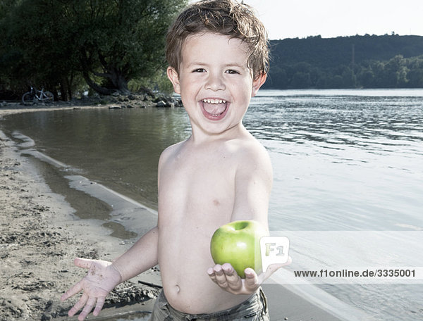 Kind hält Apfel am Fluss