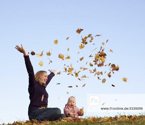 Mutter und Baby werfen Herbstlaub