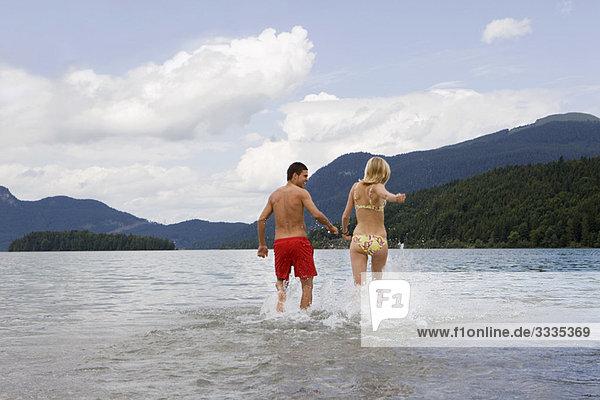 Ein Paar läuft ins Wasser.