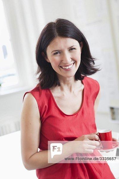 Frau in rotem Kleid mit rotem Becher