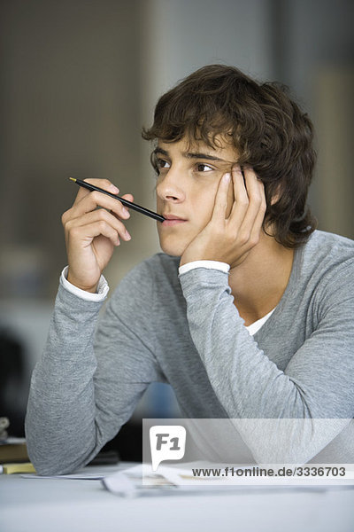 Young man with pen in mouth leaning on elbow  idly looking away