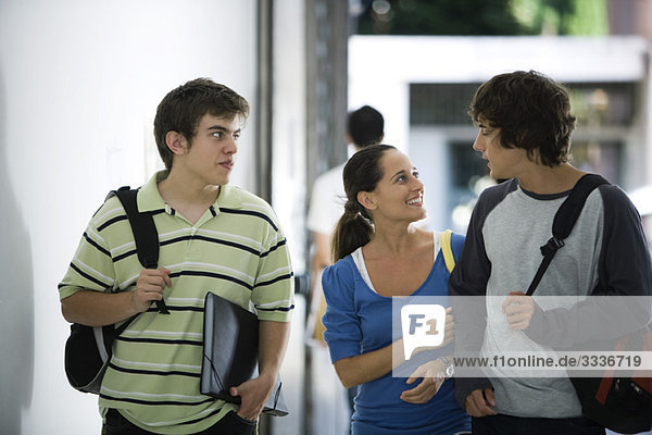 Male and female students walking and chatting together