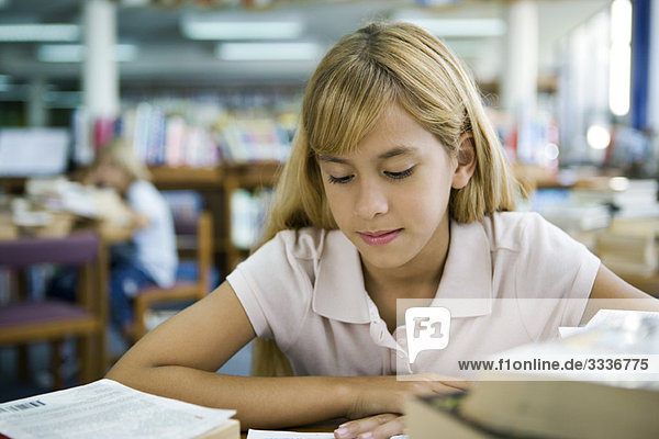 Preteen girl studying in library