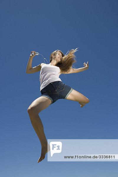 Junge Frau beim Tanzen  Springen im Freien