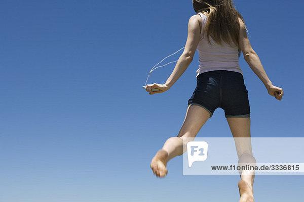Junge Frau hörtMP3-Player  springt in der Luft