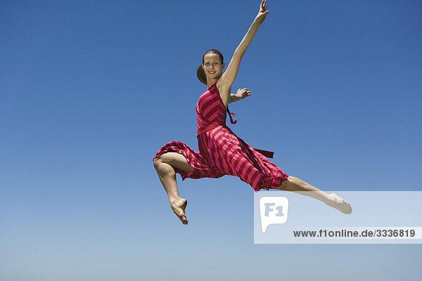 Junge Frau springt  mitten in der Luft