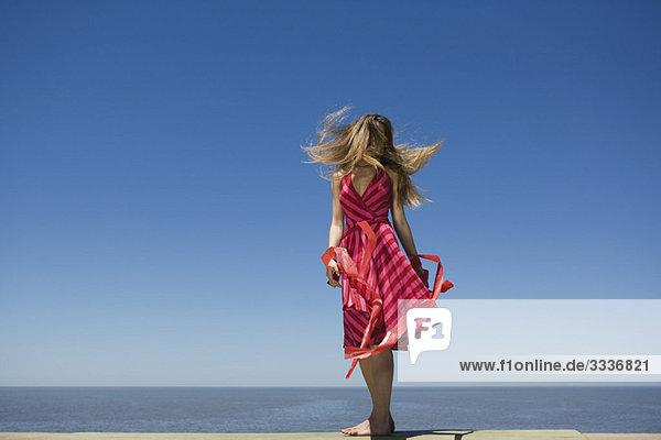 Junge Frau am Strand genießt Sonnenschein  Haare werfen