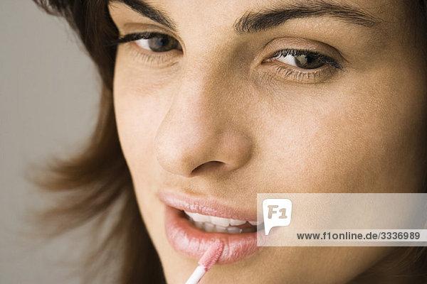 Junge Frau beim Auftragen von Lippenglanz mit Lippenpinsel und Mund