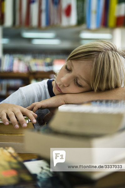 Boy resting head on arms asleep in library