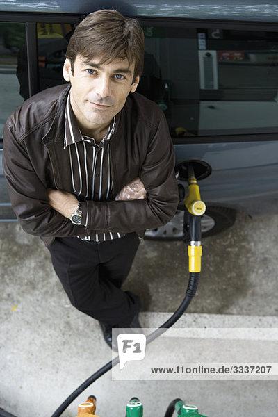 Stehender Mann mit gefaltetem Tankfahrzeug an der Tankstelle