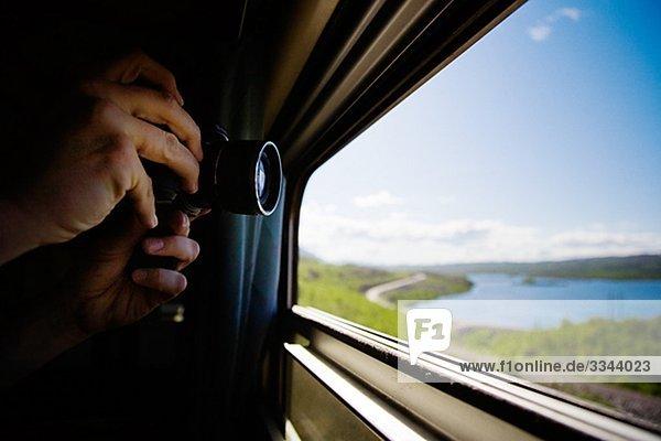 Mann Fotografieren durch ein Zugfenster  Schweden.