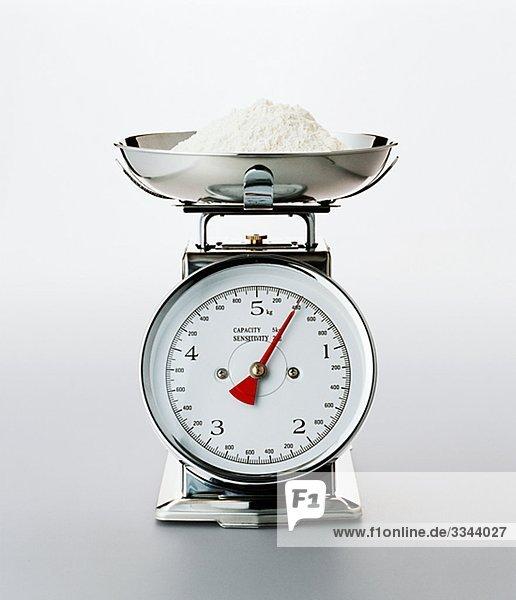 Ein Küchenwaage mit Mehl.
