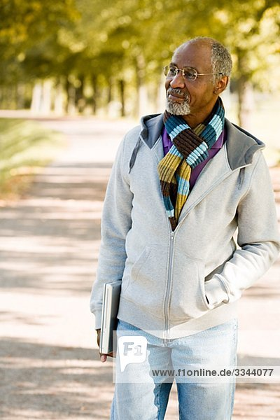 Senior man walking in a park with a laptop  Sweden.
