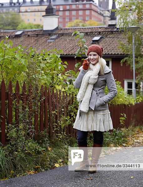 Eine Frau stehend von einem roten Zaun im Herbst  Schweden.