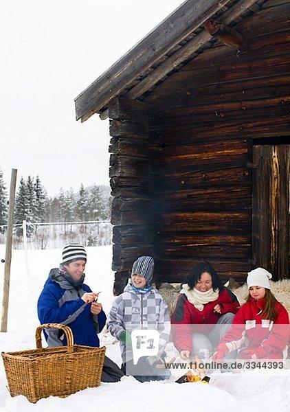 Family taking a break by a mountain hut  Sweden.