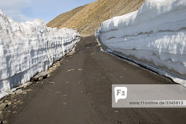 Snow bank and a road  Spitsbergen  Svalbard  Norway.
